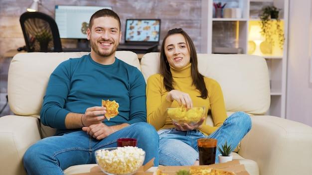 Homem barbudo alegre rindo enquanto assiste a um filme com a namorada e comendo pizza. pipoca e refrigerante na mesa de centro.