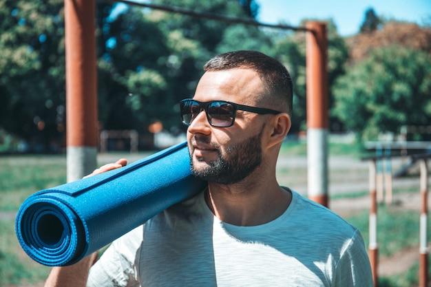 Homem barbudo alegre sorridente de aptidão com tapete de ioga em pé ao ar livre. jovem praticando exercícios de fitness ioga ao ar livre.
