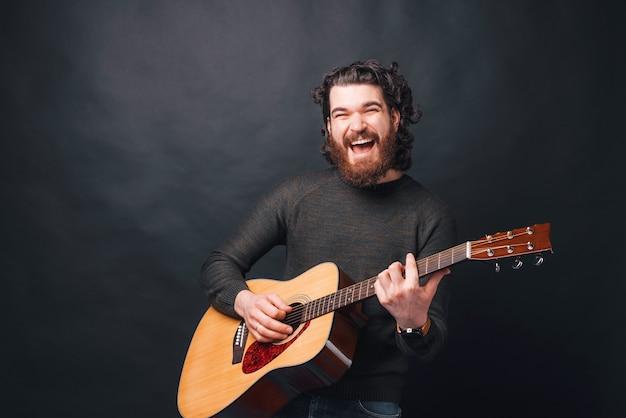 Homem barbudo alegre tocando violão perto de uma parede escura