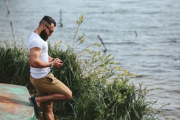 Homem barbudo americano parece na margem do rio com uma jaqueta azul