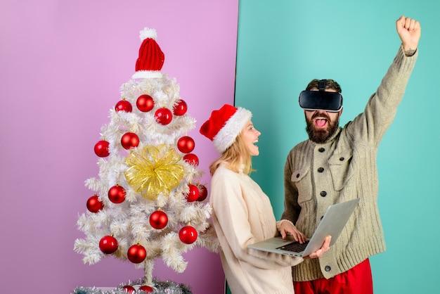 Homem barbudo animado com óculos d virtual mulher com chapéu de papai noel com tecnologia laptop d realidade virtual