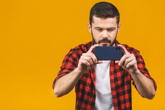 Homem barbudo animado em camisa xadrez jogando no smartphone isolado sobre parede amarela.