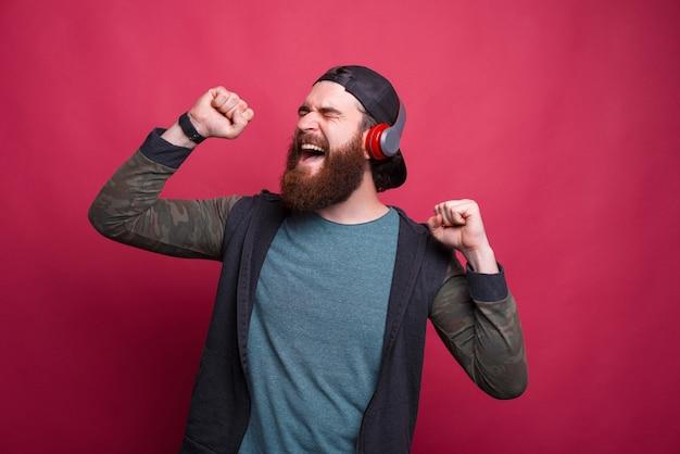 Homem barbudo animado está cantando enquanto ouve a música através de fones de ouvido