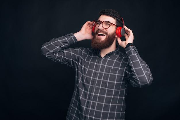 Homem barbudo animado está cantando enquanto ouve a música através de um fone de ouvido vermelho.