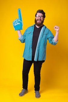 Homem barbudo animado está fazendo o gesto vencedor enquanto usava uma luva de fã