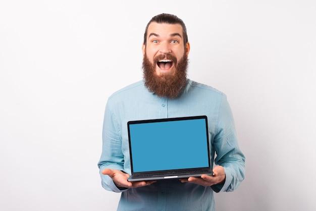 Homem barbudo animado está mostrando para a câmera a tela do laptop.