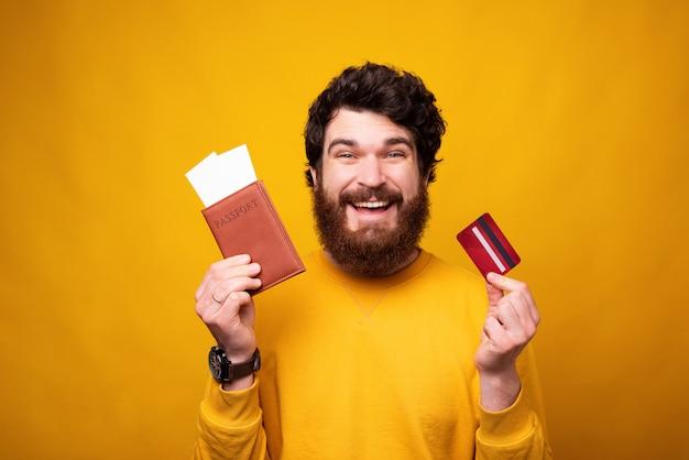 Homem barbudo animado está segurando seu passaporte e alguns bilhetes que pagou com cartão.