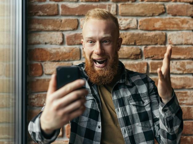 Homem barbudo animado, usando telefone celular, assistindo futebol online, apostas esportivas, sucesso de comemoração