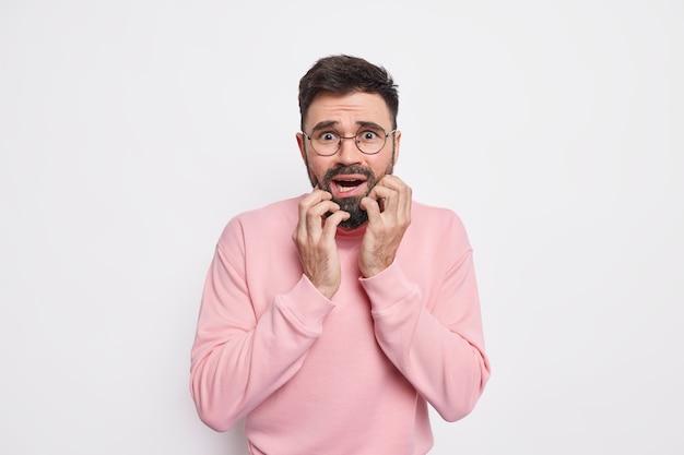 Homem barbudo ansioso assustado estando em pânico agarra o rosto se sente preocupado