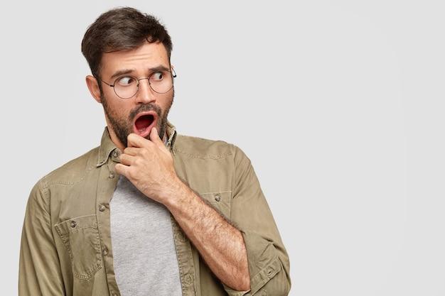 Homem barbudo ansioso e perplexo segura o queixo e olha de lado com expressão assustada, assustado com os preços altos