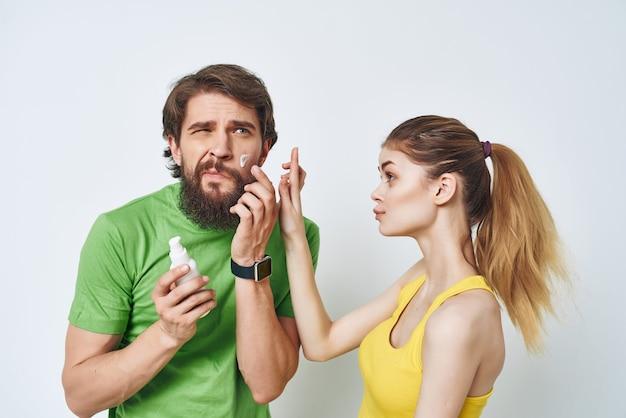 Homem barbudo ao lado de uma mulher fazendo a barba no banheiro