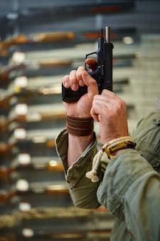 Homem barbudo aperta o parafuso da pistola na loja de armas