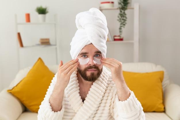 Homem barbudo aplicando tapa-olhos no rosto. rugas e cuidados domiciliares de rosto para homens.