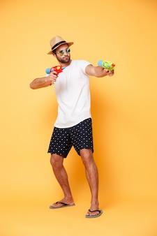 Homem barbudo apontando com pistola de água