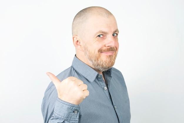 Homem barbudo apontando o polegar para trás