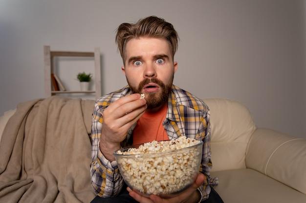 Homem barbudo assistindo a um filme ou jogos de esporte na tv, comendo pipoca em casa durante o campeonato de cinema à noite e