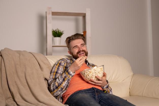 Homem barbudo assistindo filme ou jogos de esporte na tv comendo pipoca em casa durante o campeonato de cinema à noite e