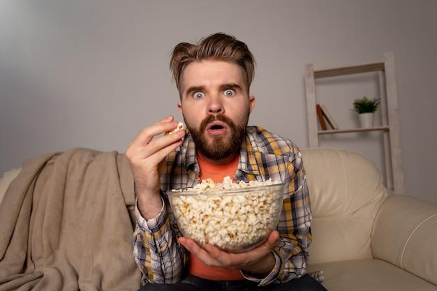 Homem barbudo assistindo filme ou jogos de esporte tv comendo pipoca em casa à noite. cinema, campeonato