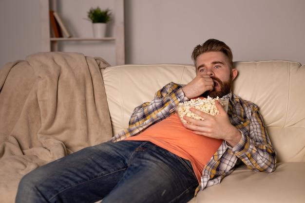 Homem barbudo assistindo filme ou jogos de esporte tv comendo pipoca em casa à noite. conceito de cinema, campeonato e lazer.