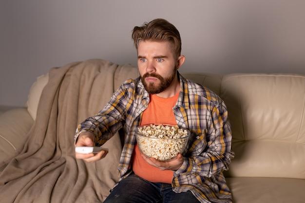 Homem barbudo assistindo filme ou jogos de esporte tv comendo pipoca em casa à noite.