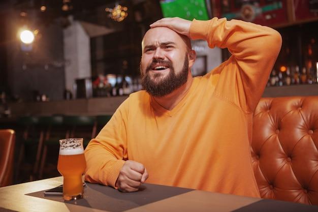 Homem barbudo assistindo futebol no pub de cerveja, olhando chateado