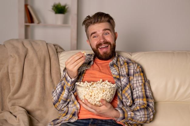 Homem barbudo assistindo tv comendo pipoca em casa à noite.