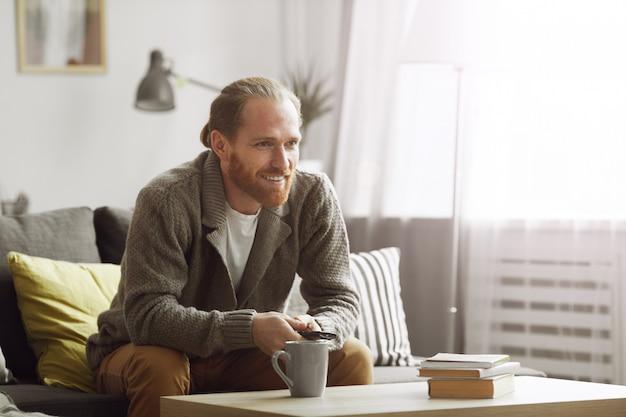Homem barbudo assistindo tv em casa