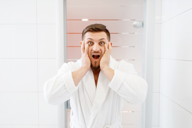 Homem barbudo assustado com sua aparência no espelho do banheiro, higiene matinal.