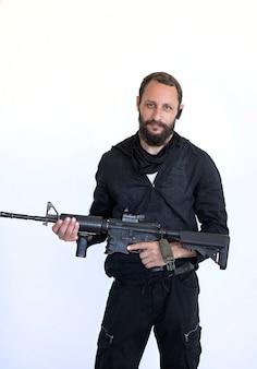 Homem barbudo, atirador com rifle pronto para atacar isolado no branco. bandido perigoso, terrorista segurando um rifle automático nas mãos. soldado das forças especiais americanas no afeganistão segura uma arma