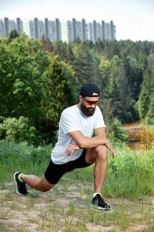 Homem barbudo atlético fazendo exercícios de treino no ginásio ao ar livre, por do sol.