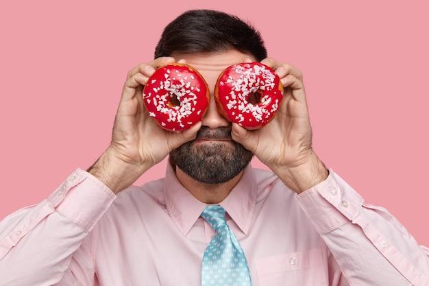 Homem barbudo atraente carrega donuts perto dos olhos, tem a barba por fazer e veste roupa formal