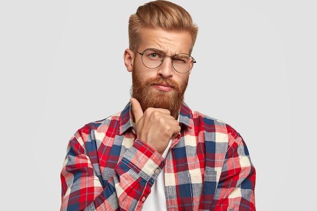 Homem barbudo atraente com barba ruiva, segura o queixo, olha pensativo, contempla sobre algo ou como resolver o problema, vestido com camisa quadriculada, isolado sobre uma parede branca.