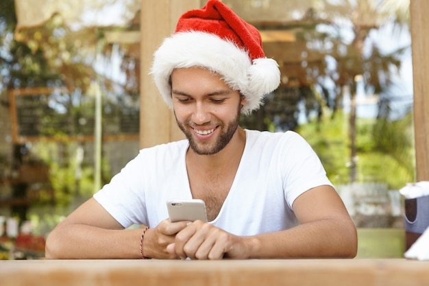 Homem barbudo atraente com chapéu de papai noel celebrando o natal em um país tropical, verificando redes sociais e lendo mensagens