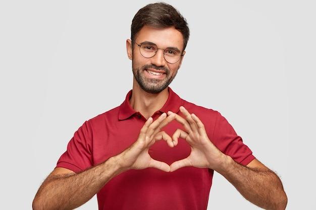 Homem barbudo atraente e amigável faz gestos de coração, sorri agradavelmente, usa óculos e camiseta vermelha, expressa amor