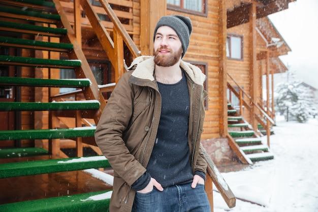 Homem barbudo atraente e pensativo em pé perto de um chalé de madeira em um clima de neve no inverno