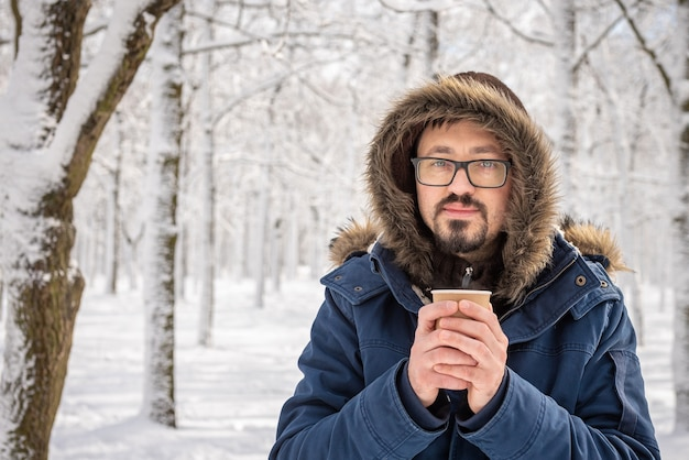 Homem barbudo atraente em óculos posando ao ar livre no frio do inverno. retrato de rua de inverno. café ou chá em um copo de papel nas mãos. um homem relaxante na caminhada de inverno no bosque nevado.