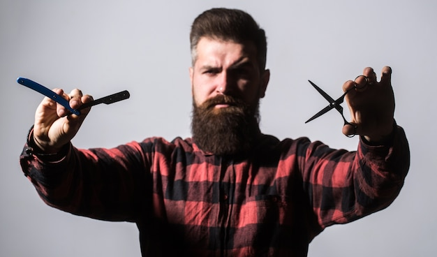 Homem barbudo, barba comprida, hipster brutal, caucasiano com bigode. tesouras de barbeiro e navalha, barbearia. homem na barbearia. corte de cabelo de homem na barbearia. corte de cabelo de homem, barbear.