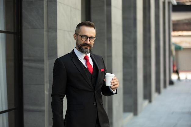Homem barbudo barba curta homem de negócios elegante caucasiano com bigode em um elegante terno preto