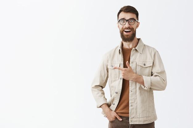 Homem barbudo barbudo alegre de óculos posando contra a parede branca