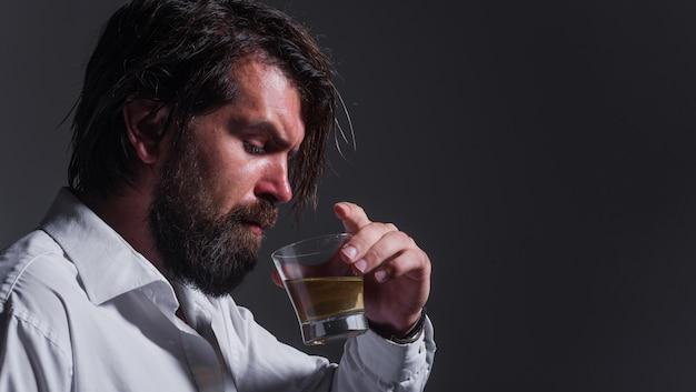 Homem barbudo bebe uísque, conhaque ou conhaque. degustação e degustação. álcool forte. o sommelier prova a bebida.