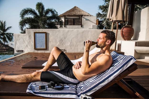 Homem barbudo bebendo cerveja à beira da piscina