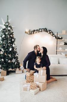 Homem barbudo beijando a esposa enquanto filha posando. família vestindo roupas pretas. sala de estar decorada com árvore de natal, guirlanda de abeto, barbante leve, caixas de presente.