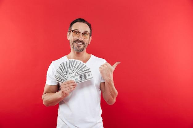 Homem barbudo bonito 30 anos de camiseta branca casual usando óculos, segurando um monte de dinheiro prêmio dólar e apontando o dedo de lado na copyspace, isolado sobre fundo vermelho