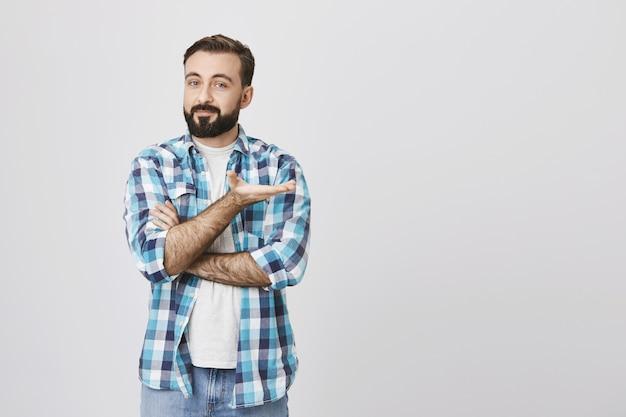 Homem barbudo bonito apresenta o produto, apontando com a mão direita