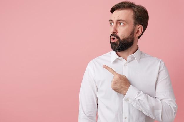 Homem barbudo bonito atordoado chama sua atenção apontando para o espaço da cópia à esquerda, isolado sobre o fundo rosa.