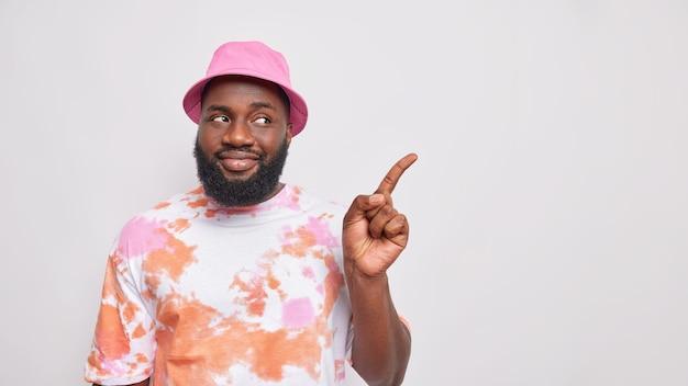 Homem barbudo bonito com barba espessa pele escura apontando para longe na área de cópia demonstra anúncio usa panamá rosa e camiseta desbotada recomendado produto mostra logotipo