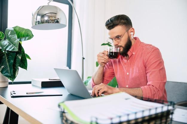Homem barbudo bonito, confiante e bem-sucedido, usando óculos e roupa casual inteligente, trabalhando no laptop