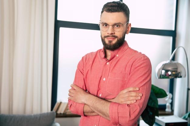 Homem barbudo bonito, confiante e feliz, usando óculos e camisa, está de pé com os braços cruzados e olhando para a câmera