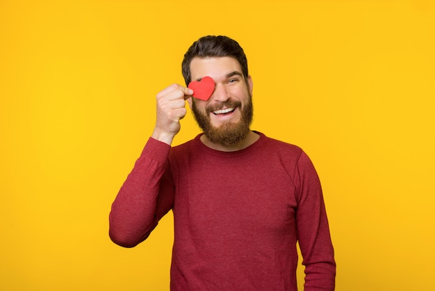 Homem barbudo bonito, de suéter vermelho, apaixonou-se e segurando um pequeno coração sobre os olhos, como um gesto, de pé sobre fundo amarelo