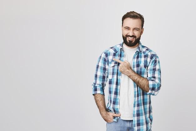Homem barbudo bonito e alegre apontando para o canto esquerdo superior e sorrindo